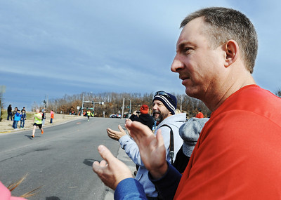 Allen Zwingle (right) of Webb City claps with the rest of the crowd as runners head for the finish of the Chilly Challenge 5K run Wednesday morning , Jan. 1, 2014, at the Joplin Family Y South. Globe | T. Rob Brown