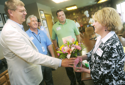 Globe/Roger Nomer (from left) Brian Berkstresser, board president, Bill Aquino, treasurer, and Andy Perigo, incoming president, welcome new United Way Director Bev Crespino-Graham with flowers on Thursday afternoon.