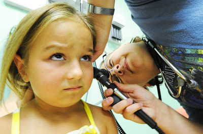 Globe/T. Rob Brown Five-year-old patient Ava Edwards, of Pittsburg, Kan., doesn't quite know what to think about her first examination by Dr. Krista Mijares, pediatrician, Friday afternoon, Aug. 3, 2012, at the Community Health Center of Southeast Kansas in Pittsburg.