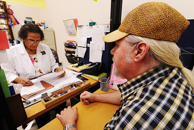 Patient Larry Wood of Joplin looks on as Doris Carson, R.N., works through his discharge paperwork Thursday morning, Aug. 29, 2013, at the Community Clinic in Joplin. The clinic is one of the many organizations that receives funding from the United Way. Globe | T. Rob Brown