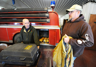 Stark City Fire Chief James Palmer (left) and Fairview Fire Chief Greg Kruse look through firefighting gear that needs replacing Thursday afternoon, Jan. 9, 2014, at the Stark City Fire Department. The two departments are hoping to combine and get a tax levy to make the necessary upgrades. Globe | T. Rob Brown