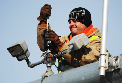Brian King, an electrical worker with Ewing Signal Construction, works on installing new sensors and cameras Wednesday morning, Jan. 8, 2014, above traffic lights at the intersection of 20th and Main streets. Globe | T. Rob Brown