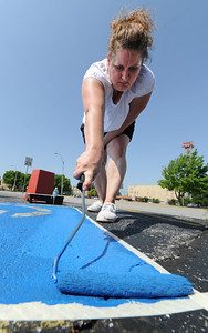 Globe/T. Rob Brown Tammy Willhoit of Neosho, a volunteer from Arvest Bank, helps paint handicap accessible parking spaces during the United Way Day of Action Friday morning, June 21, 2013, at the Community Clinic.