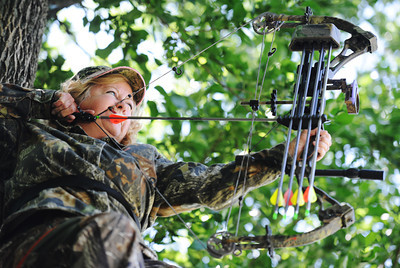 Globe/T. Rob Brown Jane Mitchell of Carl Junction takes aim with her compound bow Wednesday afternoon, June 12, 2013, from a tree stand on her property.