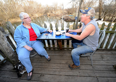 Sue Burrack, left and Dennis Robbins enjoy some conversation on the deck at The River's Bend on Shoal Creek near Reddings Mill. Robbins grandfather was a second cousin to country legend Marty Robbins and Dennis said he enjoys the live jam sessions at the bar and grill. Globe | Laurie Sisk