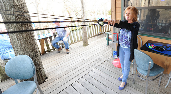 Co-owner of River's Bend Ann Galbreath launches a water balloon across Shoal Creek from the deck of her bar and grill on Tuesday night. Globe | Laurie Sisk