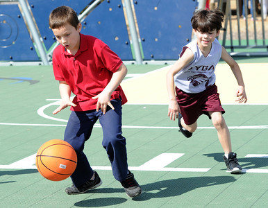 Eight-year-old Jett Beal, right, tries to catch up to nine-year-old Jerimiah Nowak as they play basketball on Friday afternoon at Cunningham Park. Globe | Laurie Sisk