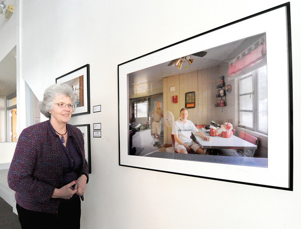 "Spiva Office Manager Linda Kyger talks about the longevity of the Photo Spiva exhibition as she stands near third place winner ""Jeff and Dad - Haunted House"" Cleveland, Ohio photographer Charles Jeffrey Mintz. Globe 