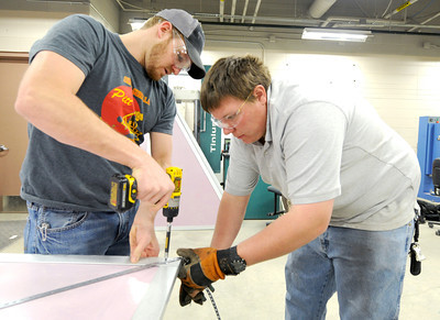 From the left: Pittsburg State seniors Austin Leake and Cody Wilkins attach reinforcement straps to a panel of their rapidly deployed shelter on Thursday at the Kansas Technology Center. Globe | Laurie Sisk