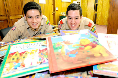 Fifteen-year-old brothers Nathan Salyer, left and 17-year-old Zach Salyer sit near the hundreds of books they have collected and plan to donate to NALA. Globe | Laurie Sisk