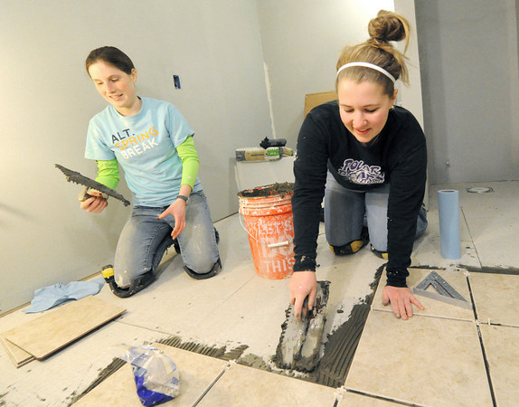 Krissy Piotroski, left and Hanna Richwine lay ceramic tiles in the bathroom of a Rebuild Joplin home at 2018 Annie Baxter on Wednesday. Globe | Laurie Sisk