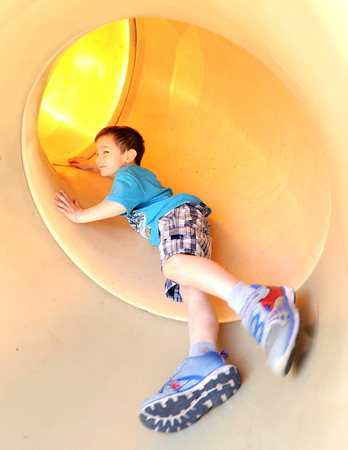 Five-year-old Jesse James enjoys a trip down a slide on Thursday at Parr Hill Park. Globe | Laurie Sisk