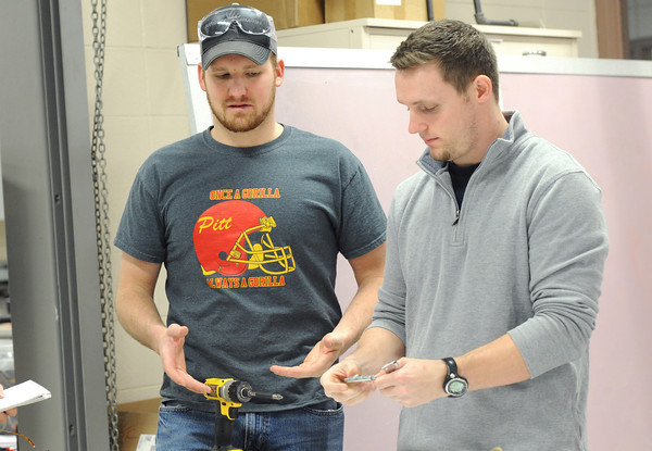 Pittsburg State University seniors Austin Leake, left and Cody Frieden discuss the advantages of snappable hinges on Thursday at the Kansas Technology Center. Globe | Laurie Sisk