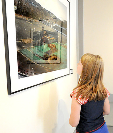 "Another entry is reflected onto a photograph entitled ""Hinchcliffe Stadium"" by Brooklyn photographer Michael Joseph Dalton as Willow Donehue, 9, of Ardmore, Okla., examines the art on Friday at Spiva. Donehue, formerly of Joplin, decided to spend part of her Spring Break at Spiva. Globe 