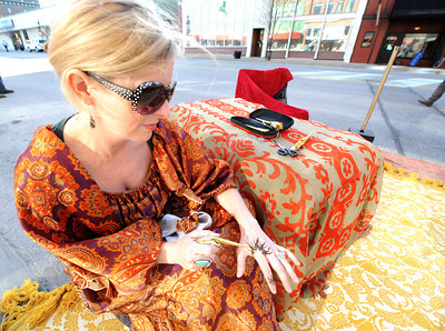 Jenifer Hall, of Kansas City's Sephirot Henna, applies a henna tatoo to her hand while waiting for the crowds to arrive at the first Third Thursday of the season on Main street. Globe | Laurie Sisk