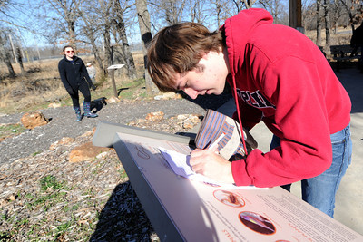 Seventeen-year-old Drew Cox logs his Joplin High School Key Club team's progress as they participate in the  Amazing Weed Whacker Challenge on Saturday at Wildcat Glades Park. The event served as both clean-up of the grounds and an educational scavenger hunt. Globe | Laurie Sisk