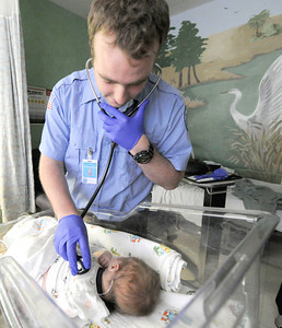 Crowder College international paramedic student Ian Kearney, of Dublin, Ireland tends to 15-day-old Cooper DeShields on Wednesday at Freeman West Hospital. Globe | Laurie Sisk