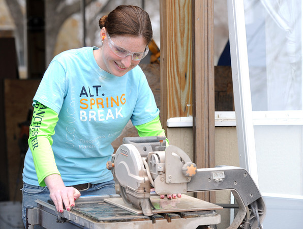 Krissy Piotroski cuts ceramic tiles for the bathroom of a Rebuild Joplin home at 2018 Annie Baxter on Wednesday. Globe | Laurie Sisk