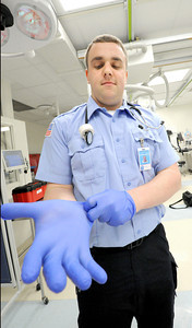 "Crowder College international paramedic student John Barron ""gloves up""  on Wednesday in the emergency room at Freeman West Hospital. Globe 
