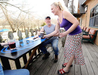 River's Bend employee Rei Alexander serves Dennis Robbins a drink on the deck of the bar and grill on Tuesday night. Globe | Laurie Sisk