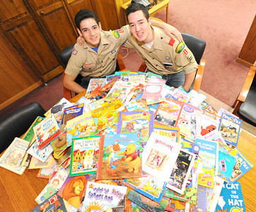 Fifteen-year-old Nathan Salyer, left and 17-year-old Zach Salyer sit near the hundreds of books they have collected and plan to donate to NALA. Globe | Laurie Sisk