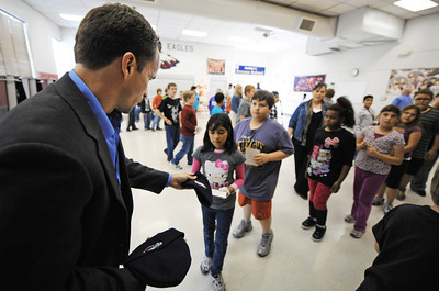 Globe/T. Rob Brown Attorney Scott Vorhees, partner with Johnson, Vorhees, and Martucci Attorneys at Law, hands out Joplin Eagles stocking caps his firm donated to Joplin School District students Friday afternoon, Nov. 30, 2012, during a stop at Emerson Elementary at Duquesne Elementary School.