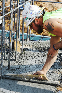 Globe/T. Rob Brown Tyler Martin, a carpenter/finisher with Branco, smooths concrete footings at the future location of the new Joplin East Middle School in Duquesne as foundation work is underway.