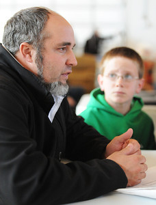 Globe/T. Rob Brown Faces of Recovery: Leland Hostetler, project coordinator with the Joplin Response for Mennonite Disaster Service, speaks as Bradley Garber, 11, looks on.